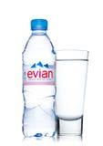 LONDON UK - MAJ 29, 2017: Flaska av Evian naturlig mineralvatten med exponeringsglas på en vit france gjorde Royaltyfria Bilder