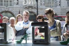 LONDON UK - MAJ 31: Gångare som fascineras med skrivaren 3D i FN Arkivbild