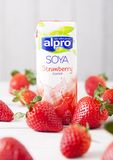 LONDON UK - MAJ 03, 2018: Packen av den Alpro sojajordgubben mjölkar drinken på träbakgrund med nya frukter Royaltyfria Bilder
