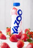 LONDON UK - MAJ 03, 2018: Plast- flaska av den Yazoo jordgubbedrinken på träbakgrund med nya frukter Royaltyfri Bild