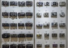 Vintage film cameras lined up on wall in chronological order starting from 1979 to 2007, beginning of digital cameras. London, UK - Mar 6, 2018: Vintage film Royalty Free Stock Images