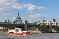 Boat travels under Southwark Bridge on the. LONDON, UK - MARCH 25, 2016: Tourist cruise boat travels under Southwark bridge stock image