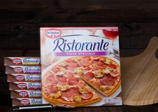 LONDON, UK - MARCH 01, 2018: Boxes of Dr.Oetker Pizza Pepperoni-Salame on wooden background with board. royalty free stock image
