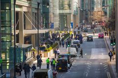 Canary Wharf street view with lols of walking business people and transport on the road. Business and modern life o. London, UK - March 15, 2017: Canary Wharf Stock Photography