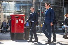 Canary Wharf street view with lols of walking business people and transport on the road. Business and modern life o. London, UK - March 15, 2017: Canary Wharf Stock Images