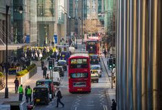 Canary Wharf street view with lols of walking business people and transport on the road. Business and modern life o. London, UK - March 15, 2017: Canary Wharf Royalty Free Stock Photography