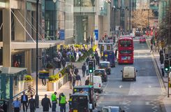 Canary Wharf street view with lols of walking business people and transport on the road. Business and modern life o. London, UK - March 15, 2017: Canary Wharf Royalty Free Stock Photos