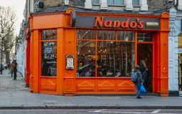 Exterior of Nando`s flame grilled PeriPeri chicken restaurant in Earl`s Court, London, UK. The chain is AfroPortuguese stock image