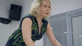 London, UK - March 12, 2019: fitness woman training on indoor bike at cycling class in sport club. Sport trainer. Practising exercise on static bike in gym stock video