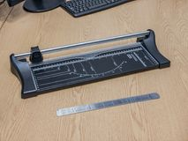 Paper cutter and ruler on a desk stock images