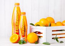 LONDON, UK - MARCH 31, 2018: Plastic bottle of Lucozade orange soft soda drink with fresh raw oranges in wood box stock photos