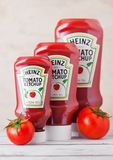 LONDON, UK - MARCH 10, 2018 : Plastic bottles of Heinz Ketchup on wood with raw tomatoes. Manufactured by H.J. Heinz Company. LONDON, UK - MARCH 10, 2018 royalty free stock image