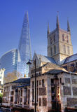 LONDON, UK - MARCH 29, 2014 Southwark Cathedral and Shadr of glass South bank walk of the river Thames Contrast modern and old arc Stock Photography