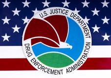 Drug Enforcement Administration Seal and US Flag. LONDON, UK - MARCH 27TH 2018: The seal or symbol of the Drug Enforcement Administration of the US Justice Royalty Free Stock Images