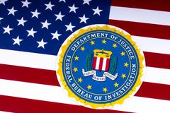 FBI Logo and the USA Flag. LONDON, UK - MARCH 26TH 2018: The seal or symbol of the Federal Bureau of Investigation, portrayed with the US flag, on 26th March Royalty Free Stock Photography