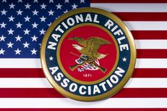 National Rifle Association Logo and US Flag. LONDON, UK - MARCH 26TH 2018: The symbol of the National Rifle Association portrayed with the US flag, on 26th March royalty free stock photography