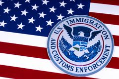 US Immigration and Customs Enforcement. LONDON, UK - MARCH 26TH 2018: The symbol of US Immigration and Customs Enforcement portrayed with the US flag, on 26th stock photos