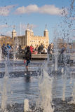 Tourists enjoy fountains with Tower of London in background. LONDON, UK - MARCH 25, 2016: Tourists enjoy fountains opposite the Tower of London Royalty Free Stock Photos