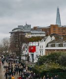 Tourists at Jubilee Walk on South Bank of River Thames with Shakespeare`s Globe, a replica of the original 1599. London, UK - March 10, 2018: Tourists at Jubilee Stock Image