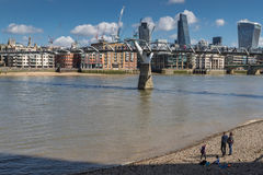 Tourists on pebble beach of Thames at low tide. LONDON, UK - MARCH 25, 2016: Tourists on pebble beach by Thames and Millennium Bridge Royalty Free Stock Photos