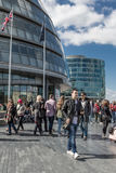 LONDON, UK - MARCH 25, 2016: Tourists on the Southbank of the Th. Ames walk past City Hall Royalty Free Stock Photo