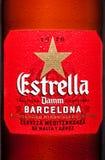 LONDON UK - MARS 21, 2017: Buteljera etiketten av Estrella Dam öl på vit bakgrund, Estrella Dam är ett pilsner öl som bryggas i l Arkivfoto
