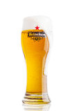 LONDON UK - MARS 23, 2017: Ett exponeringsglas av Heineken Lager Beer på vit Heineken Lager Beer är ett öl för blekt lager som pr Arkivfoto