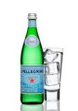 LONDON UK - MARS 30, 2017: Flaska med exponeringsglas av San Pellegrino mineralvatten på vit San Pellegrino är ett italienskt mär Royaltyfri Bild