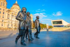 Bronze statue of the Beatles at the Merseyside in Liverpool, UK. Liverpool, UK - May 17 2018: Bronze statue of the Beatles stands at the Pier Head on the side of stock photos