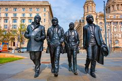 Bronze statue of the Beatles at the Merseyside in Liverpool, UK. Liverpool, UK - May 17 2018: Bronze statue of the Beatles stands at the Pier Head on the side of royalty free stock photos