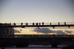 London cityscape across the River Thames with a view of people crossing the Millennium Bridge, London, stock photography