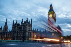 Double-decker bus passes pedestrians walking in front of Big Ben and Houses of Parliament Stock Photos