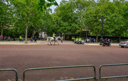 London, UK - May 11, 2017: Metropolitan Police on horseback and. Motorbikes outside royal residence in The Mall. Railings and road in the foreground Royalty Free Stock Photos