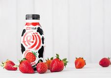 LONDON, UK - MAY 03, 2018: Plastic bottle of Muller strawberry drink on white wooden background with fresh berries. LONDON, UK - MAY 03, 2018: Plastic bottle of Stock Photos