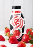 LONDON, UK - MAY 03, 2018: Plastic bottle of Muller strawberry drink on white wooden background with fresh berries. LONDON, UK - MAY 03, 2018: Plastic bottle of Stock Images