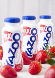 LONDON, UK - MAY 03, 2018: Plastic bottles of Yazoo strawberry drink on wooden background with fresh fruits. LONDON, UK - MAY 03, 2018: Plastic bottles of Yazoo Royalty Free Stock Photos