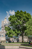 LONDON, UK - MAY 12, 2016: Tourists andTower Bridge on a sunny S. Pring day, with lush green tree in foreground Royalty Free Stock Photography