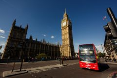 Double-decker bus passes pedestrians walking in front of Big Ben and Houses of Parliament Royalty Free Stock Photography