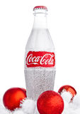 LONDON, UK - NOVEMBER 07, 2016: Classic bottle Of Coca-Cola on white background with christmas toys and snow Stock Image