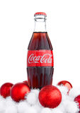 LONDON, UK - NOVEMBER 07, 2016: Classic bottle Of Coca-Cola on white background with christmas toys and snow Stock Images