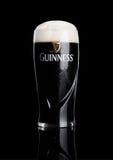 LONDON UK - NOVEMBER 29, 2016: Exponeringsglas av Guinness original- öl på svart bakgrund Guinness öl har producerats efter 1759  Royaltyfri Foto