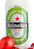 LONDON UK - NOVEMBER 11, 2016: Flaska av Heineken Lager Beer som täckas med snö och röda julbollar Heineken är flaggskepppren Fotografering för Bildbyråer