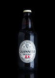 LONDON, UK - NOVEMBER 29, 2016: Guinness extra stout beer  bottle on black background. Guinness beer has been produced since 1759 Stock Images