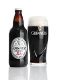 LONDON, UK - NOVEMBER 29, 2016: Guinness extra stout beer bottle and glass on white background. Guinness beer has been produced s. Ince 1759 in Dublin, Ireland royalty free stock photos