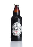 LONDON, UK - NOVEMBER 29, 2016: Guinness extra stout beer  bottle on white background. Guinness beer has been produced since 1759 Royalty Free Stock Photos