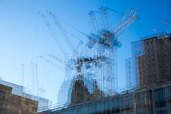 Multiple exposure image of building construction site in the centre of London. Cranes and concrete contraction against of blue sky. London, UK - November 30 Royalty Free Stock Photo
