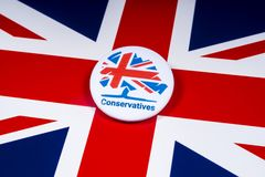 Conservative Party Badge over the UK Flag. London, UK - November 18th 2018: A Conservative Party pin badge over the UK flag royalty free stock photos