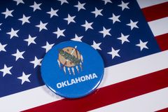 State of Oklahoma in the USA. London, UK - November 15th 2018: The symbol of the state of Oklahoma, pictured over the flag of the United States of America royalty free stock image