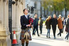 LONDON, UK - NOVEMBER 19, 2017: Young male musician playing the bagpipes to entertain tourists and Londoners. Beautiful autumn day. LONDON, UK - NOVEMBER 19 stock image