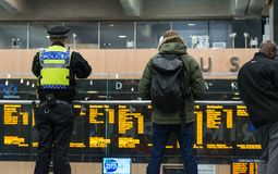 LONDON, UK - October 17th, 2017: british transport police officer watching Travelers watching the information departure. Boards for their gate number at the Stock Images